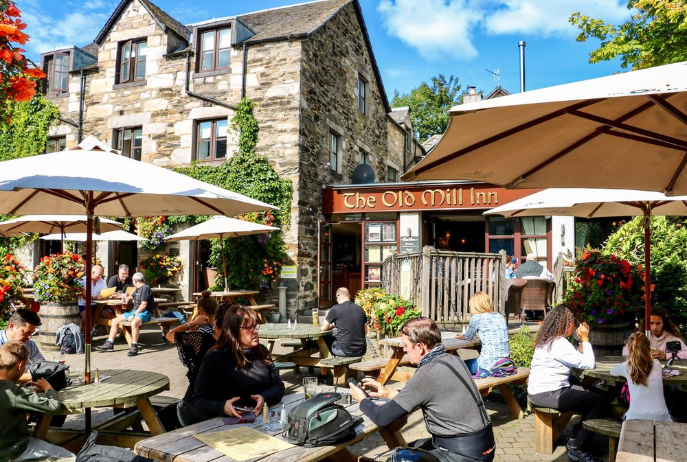 Photo of the Old Mill exterior with people eating & drinking