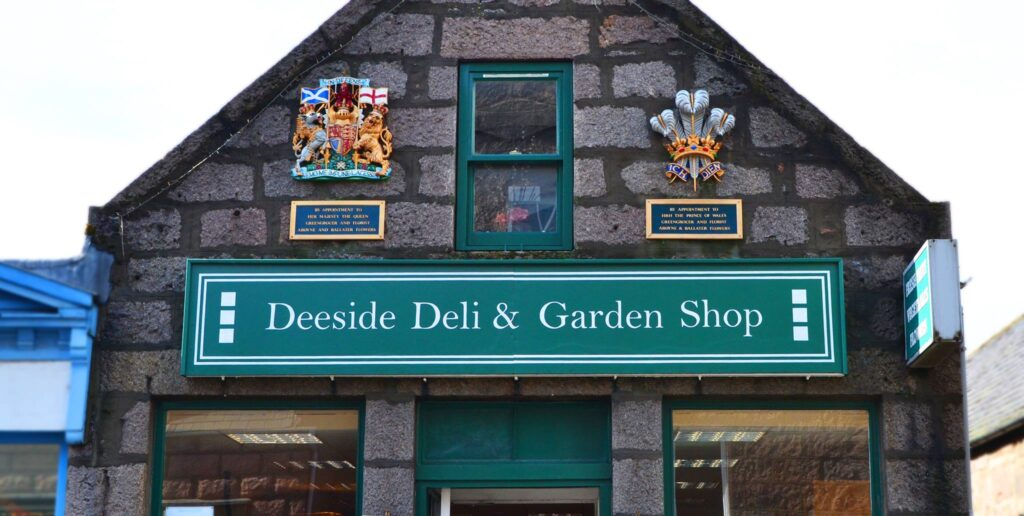 Deeside Deli & Garden Shop exterior shop sign showing its royal warrants